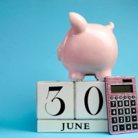 Calendar date for End of Financial Year, 30 June, with piggy bank and pink calculator